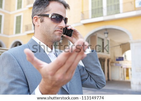 Portrait of an unhappy businessman having a discussion on his smart phone while visiting a classic city. - stock photo
