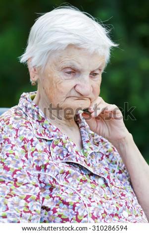 Portrait of an unhappy elderly woman - stock photo
