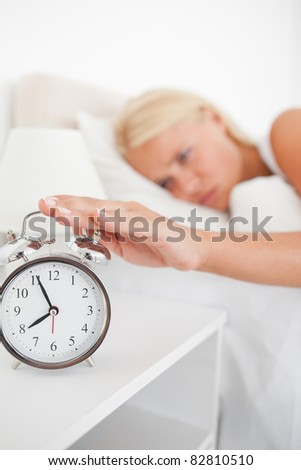 Portrait of an unhappy woman switching off her alarm clock in her bedroom - stock photo