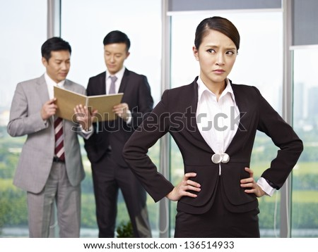 portrait of an unhappy young asian businesswoman with her colleagues talking in the background.