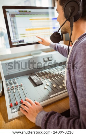 Portrait of an university student mixing audio in a studio of a radio - stock photo