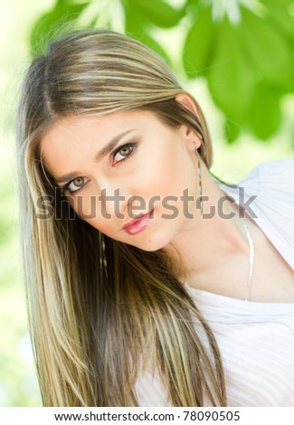 Portrait of an young beautiful  girl in the nature - green leafs in background - stock photo