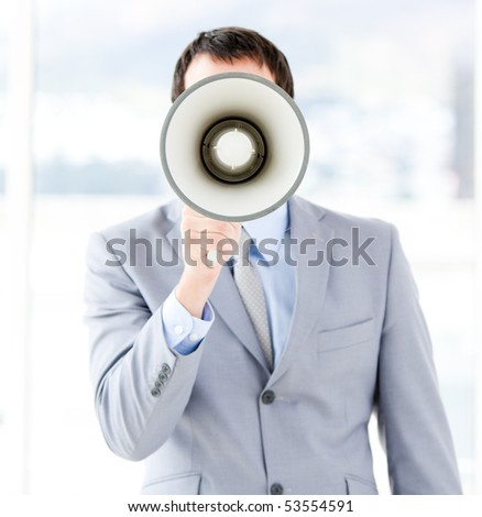 Portrait of an young businessman using a megaphone in the office