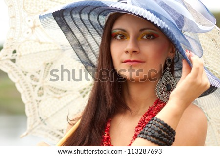 Portrait of an young lady in blue hat with an umbrella