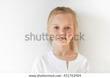 Portrait of angel-like child in white morning light in studio. Little European girl with blond hair looking attractive and balanced showing neutral emotions and radiating tranquility. - stock photo