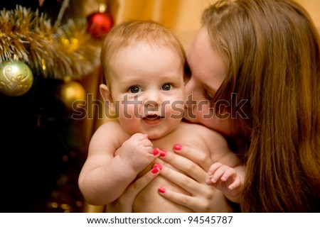 Portrait of angelic baby and his mother near the Christmas tree