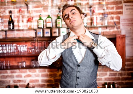 Portrait of angry and stressed barman with bowtie behind the bar with alcoholic drinks around. Stressful lifestyle of barista concept - stock photo