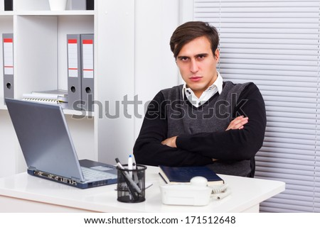 Portrait of  angry businessman sitting in her office,Angry businessman - stock photo