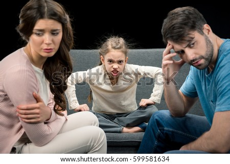 portrait of angry daughter and upset parents isolated on black, family problems concept