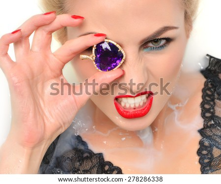 Portrait of angry fashion sexy woman face lying in milk bath with splashes red lips and nails holding gold pendant with big amethyst and diamonds on white background - stock photo