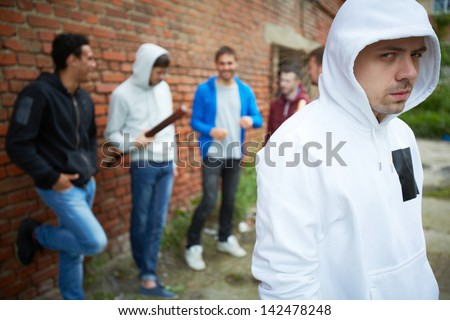 Portrait of angry guy looking at camera with his friends on background - stock photo
