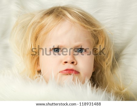 portrait of angry little girl in bed - stock photo