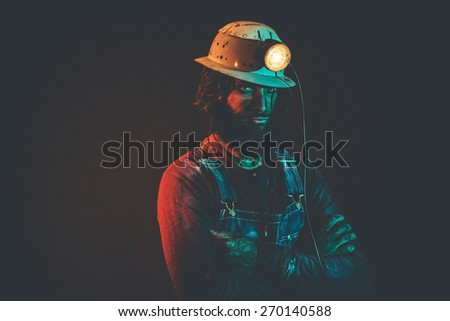 Portrait of Angry Looking Male Miner Wearing Lit Safety Helmet Lamp and Standing with Arms Crossed Illuminated with Blue Light