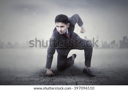 Portrait of angry male entrepreneur punching the ground, shot with city background - stock photo