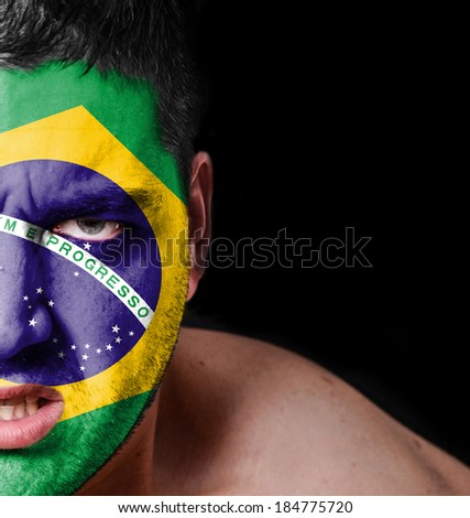 Portrait of angry man with painted flag of Brazil - stock photo