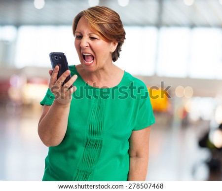 portrait of angry mature woman talking on telephone - stock photo