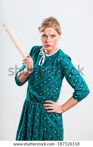 Portrait of angry retro housewife holding rolling pin,Angry retro housewife - stock photo