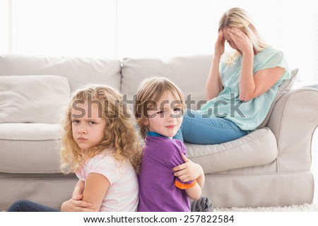 Portrait of angry siblings sitting arms crossed with sad mother on sofa at home - stock photo