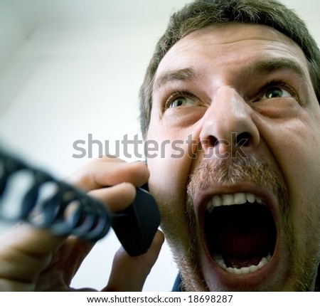 Portrait of angry stressed businessman screaming at the phone - stock photo