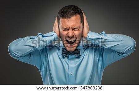 Portrait of angry upset young man in blue shirt and butterfly tie closes his ears with hands, yelling isolated on gray studio background. Negative human emotion, facial expression. Closeup - stock photo