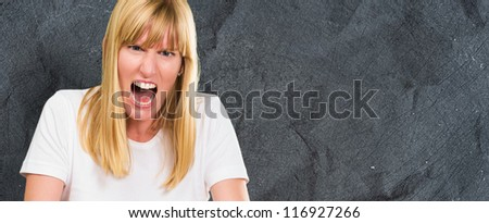 Portrait Of Angry Woman against a dark concrete background