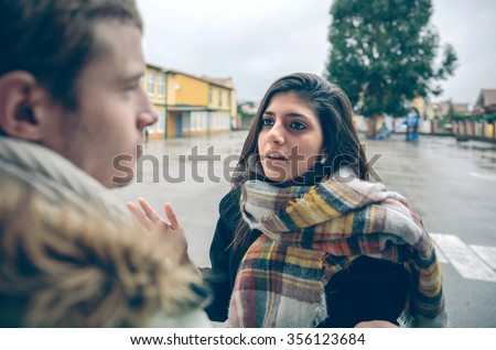 Portrait of angry woman having argument to young man during a hard quarrel outdoors. Couple relationships and problems concept. - stock photo