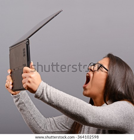 Portrait of angry woman screaming at  her laptop against gray background