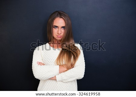 Portrait of angry woman standing with arms folded over gray background - stock photo