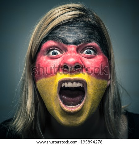 Portrait of angry woman with flag of Germany painted on face. - stock photo