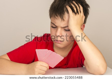portrait of angry young boy playing cards - stock photo