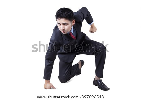 Portrait of angry young businessman punching the floor, isolated on white background