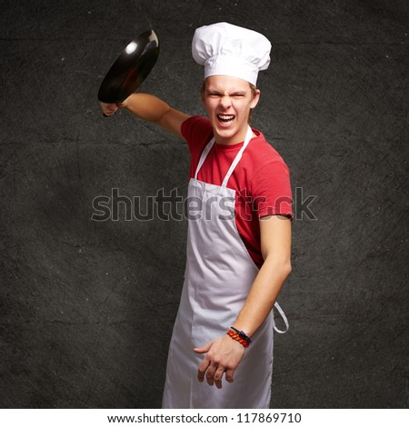 portrait of angry young cook man hitting with pan against a grunge wall - stock photo