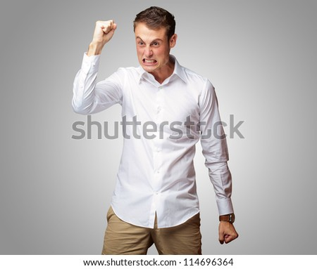 Portrait Of Angry Young Man Clenching His Fist on gray background