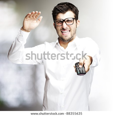 portrait of angry young man using tv control indoor - stock photo