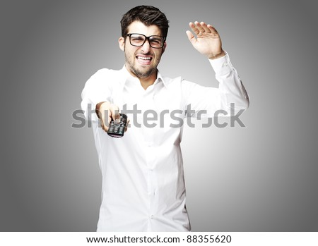 portrait of angry young man using tv control over grey background