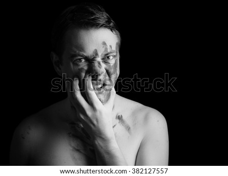 Portrait of angry young man with paint on his face on dark background. Black and white toned.