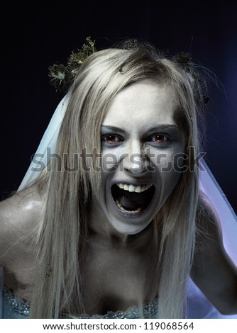 Portrait of angry zombie corpse bride looked scary and standing at dark background. shot in studio