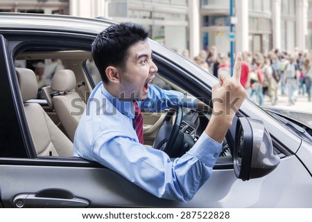 Portrait of annoyed male entrepreneur screaming and showing middle finger while driving a car - stock photo
