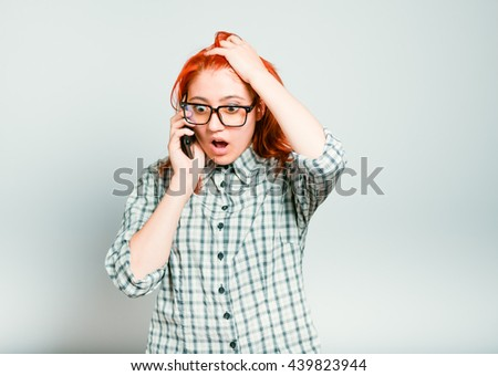 portrait of annoyed woman speaks on the phone, the redhead with glasses, isolated on a gray background