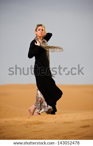 Portrait of arabic way dressed woman in yellow desert. - stock photo