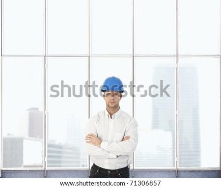 Portrait of architect designer man standing at skyscraper window. Copyspace.? - stock photo