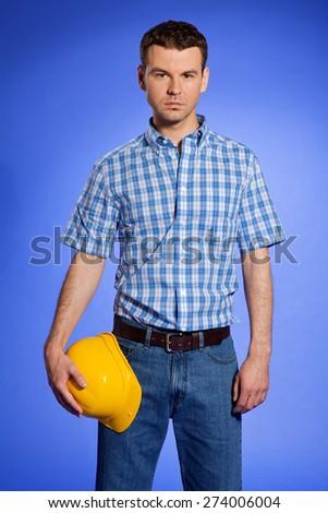 Portrait of architect holding hardhat - stock photo