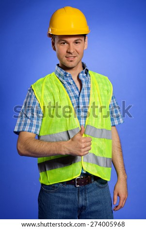 Portrait of architect in coveralls and hardhat showing thumbs up sign - stock photo