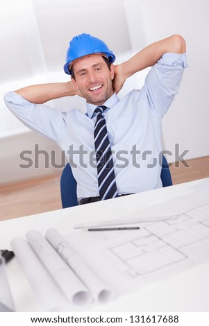 Portrait Of Architect Relaxing With Blueprint In The Office - stock photo
