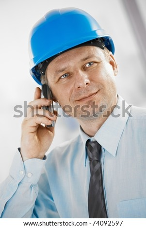 Portrait of architect talking on mobile, looking at camera, smiling. - stock photo
