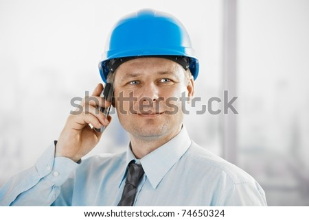 Portrait of architect talking on mobile, looking at camera, smiling.? - stock photo