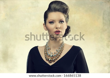 portrait of aristocratic fashion female posing with elegant hair-style, black dress and big necklace. Looking in camera with sensual eyes    - stock photo