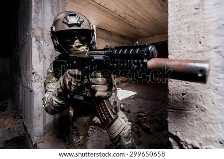 Portrait of armed soldier in mask and helmet during the military operation in a buiding/Armed soldier during the military operation in a buiding - stock photo