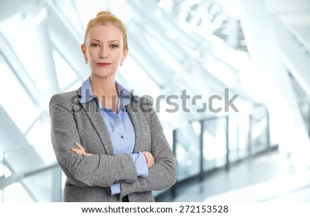 Portrait of arms crossed bank employee standing at office while looking at camera and arms crossed. Business person.  - stock photo