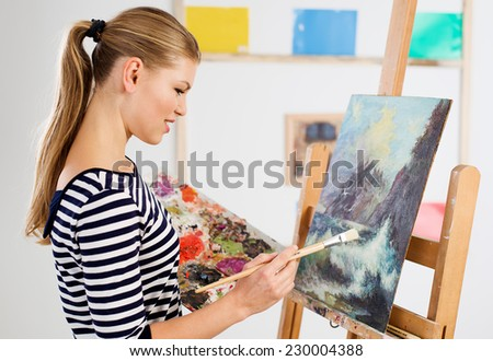 Portrait of artist female painting with paintbrush and oil colors in studio. Young attractive woman working on canvas.  - stock photo